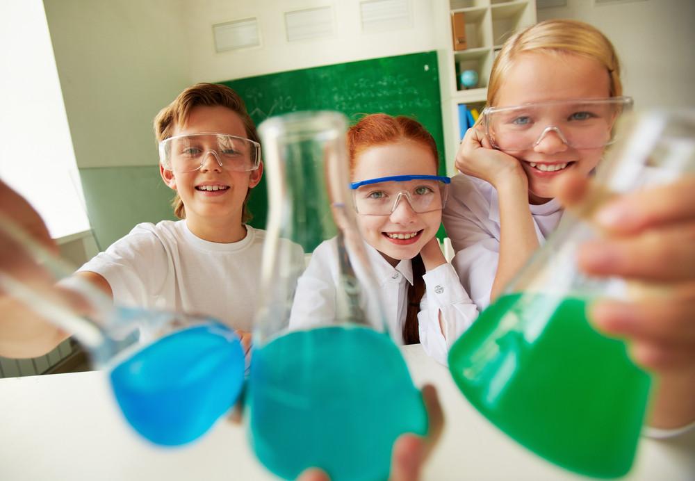 Three Happy Schoolchildren Holding Tubes With Chemical Liquids