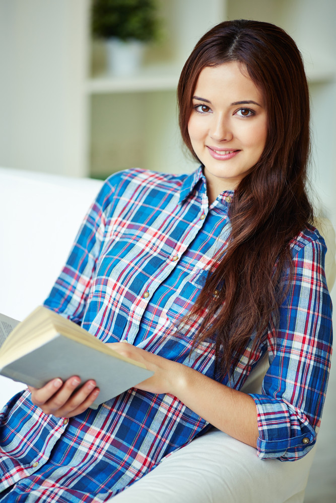 Pretty Teenage Girl With Open Book Looking At Camera