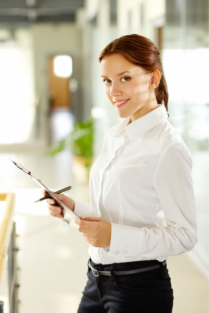 Young Businesswoman With Document Looking At Camera And Smiling