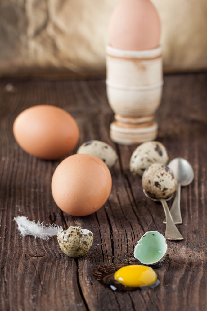 Broken Quail Egg With The Leaked Yolk And Chicken Eggs
