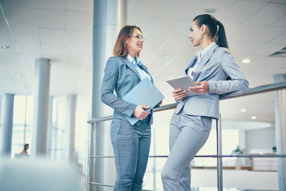 Image Of Two Elegant Businesswomen Interacting At Meeting