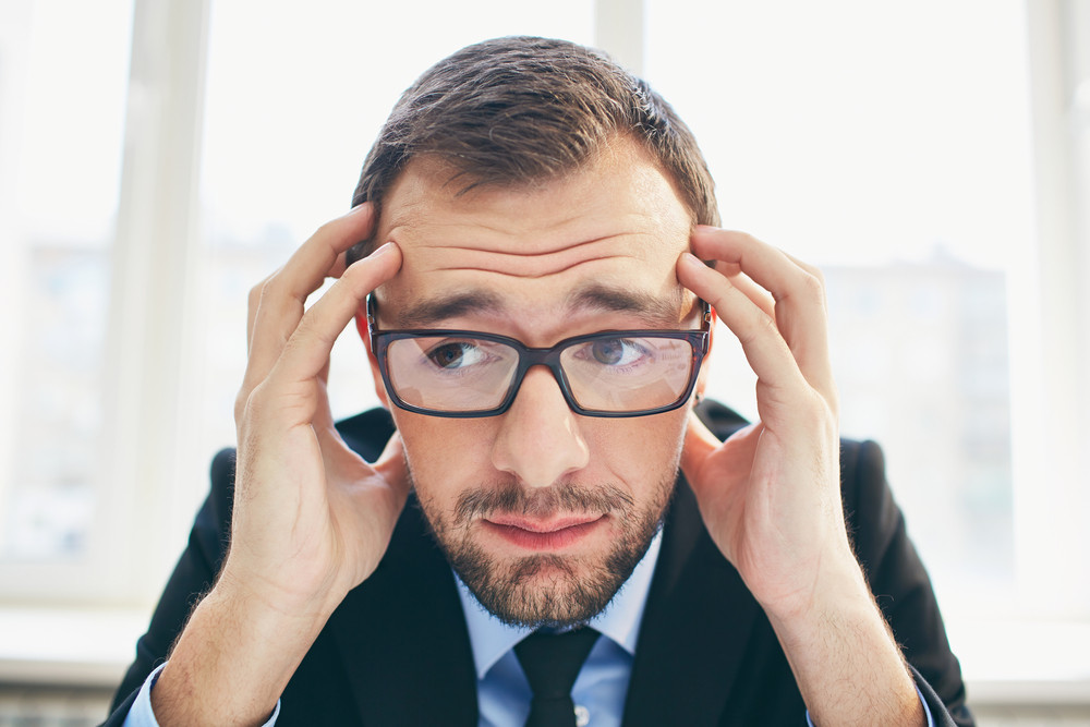 Frustrated Businessman In Eyeglasses Touching His Head