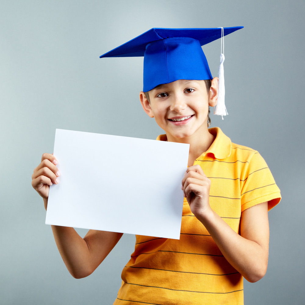 Portrait Of Happy Boy With Blank Paper Looking At Camera