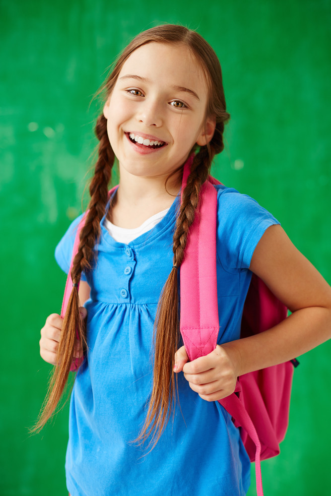 Cheerful Child With Backpack Looking At Camera In Isolation