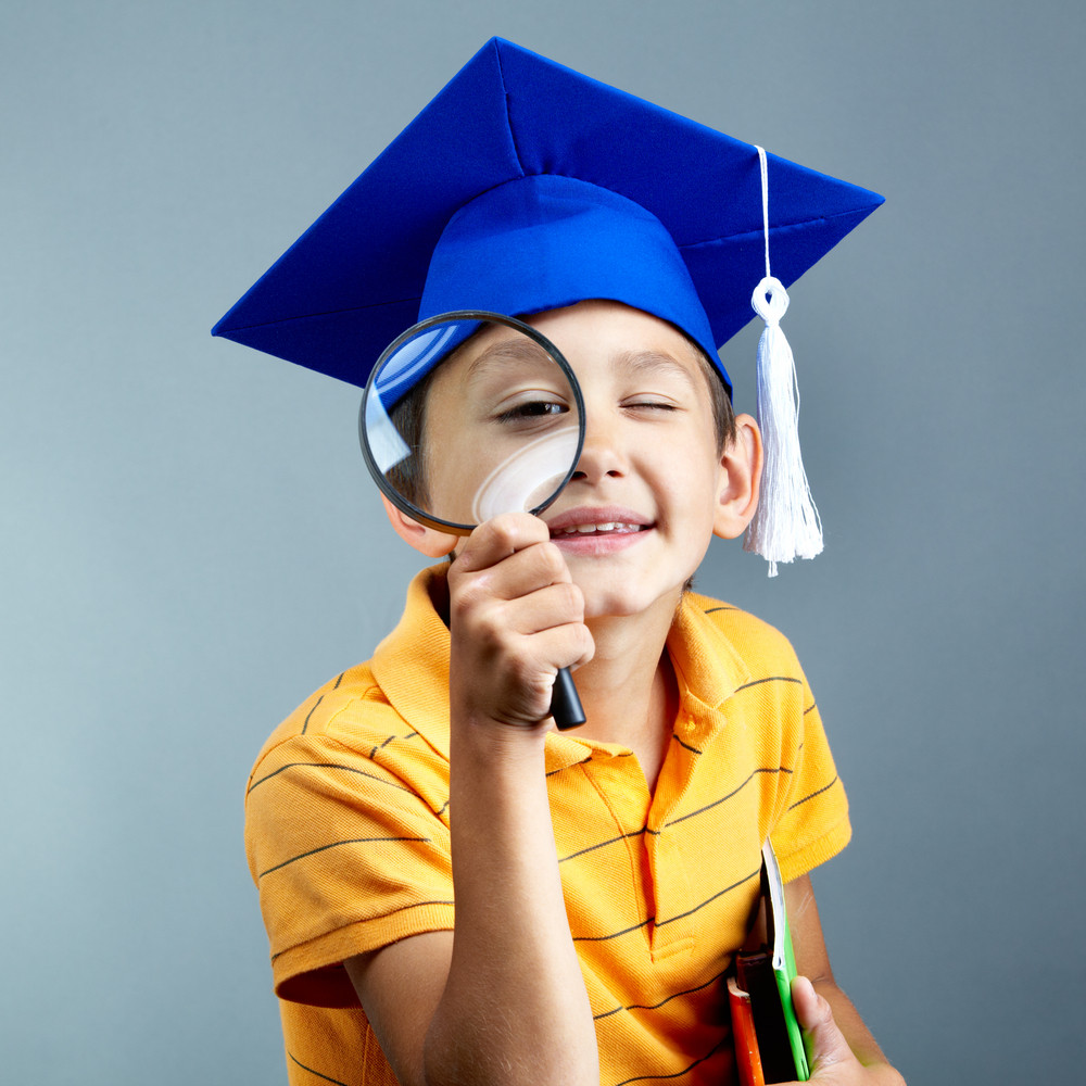 Portrait Of Curious Boy In Graduation Hat Looking Through Magnifying Glass