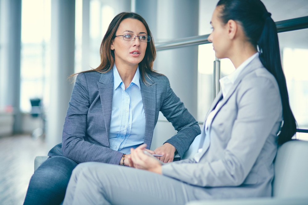 Image Of Two Businesswomen Sitting And Discussing New Ideas