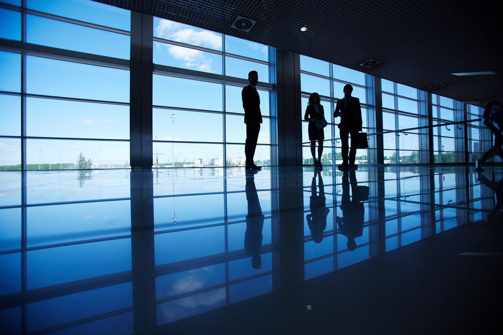 Silhouettes Of Several Office Workers Standing By The Window
