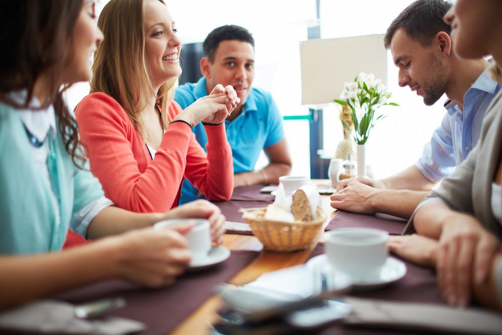 Portrait Of Happy Teenage Friends Sitting In Cafe