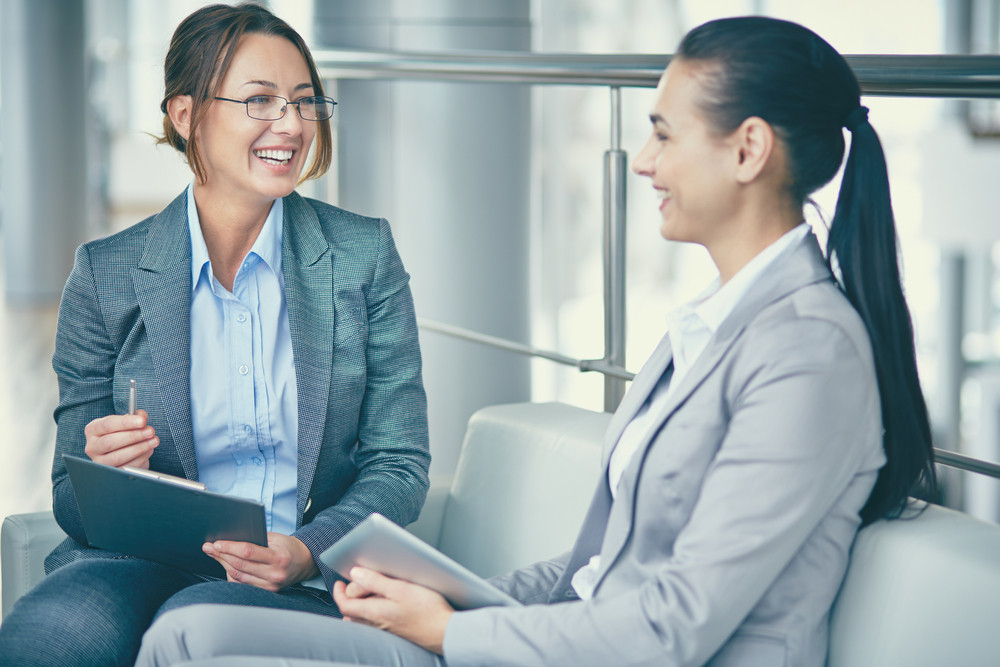 Image Of Two Happy Businesswomen Sitting And Talking