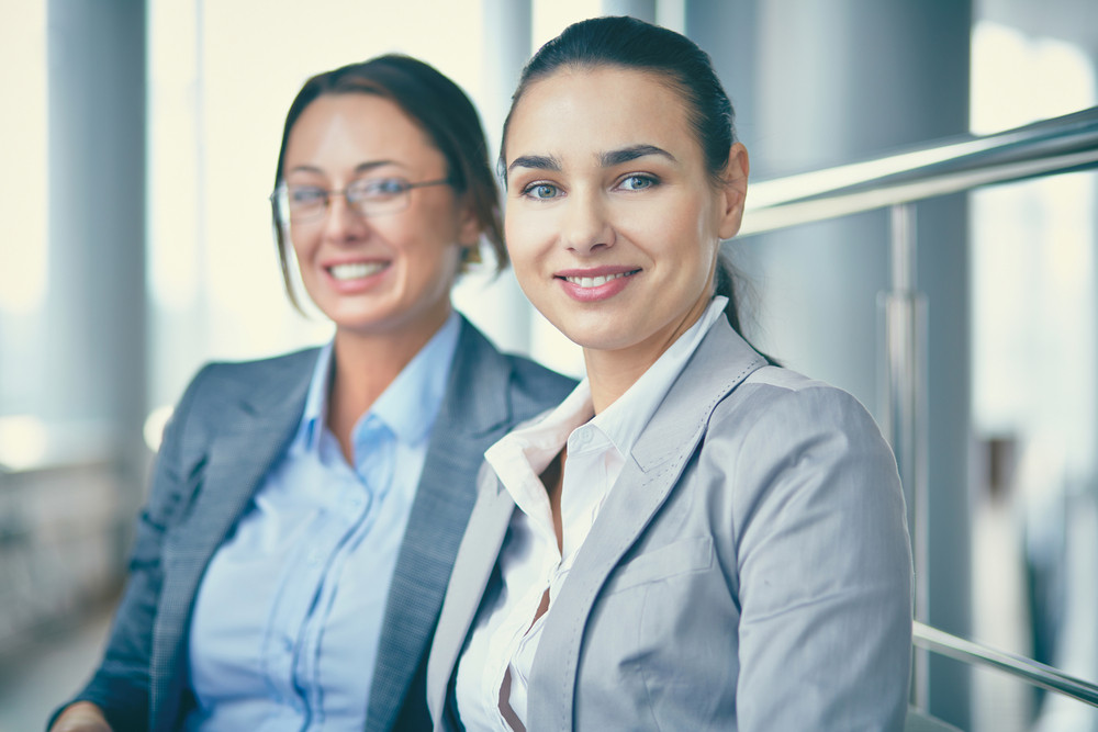 Image Of Confident Businesswomen Looking At Camera With Her Colleague Behind