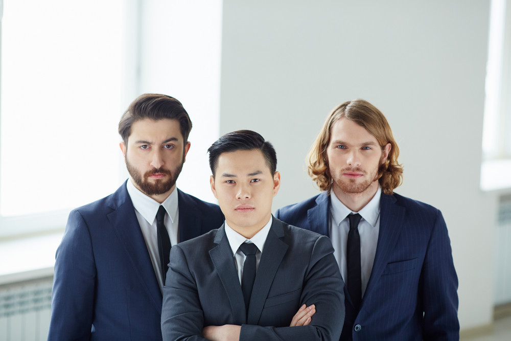 Team Of Serious Businessmen Looking At Camera
