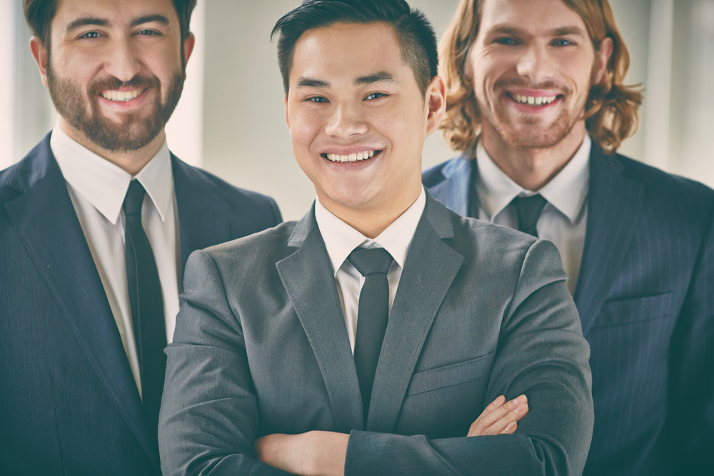 Closeup Portrait Of A Confident Business Leader Looking At Camera With His Partners On Background