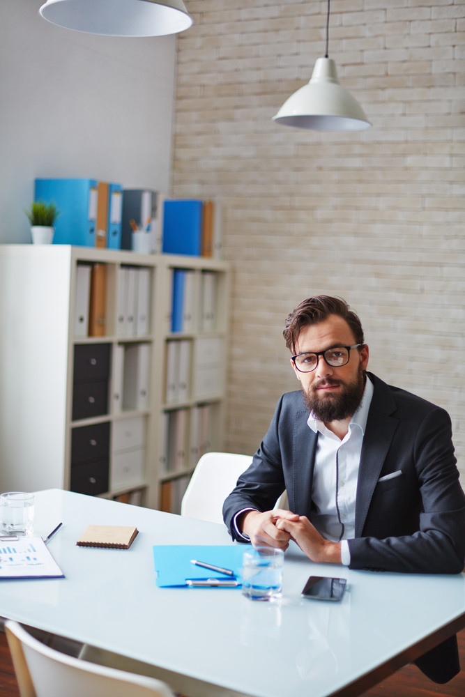Young Businessman With Beard Sitting At Workplace In Office
