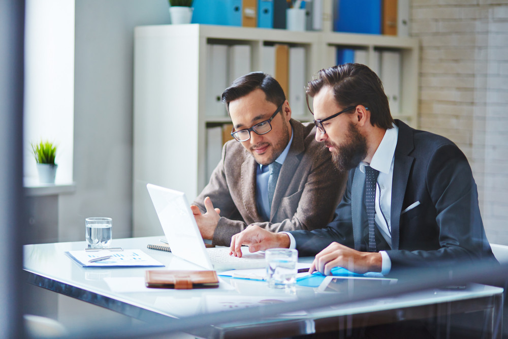 Young Businessman With Beard Showing New Project To His Colleague In Office