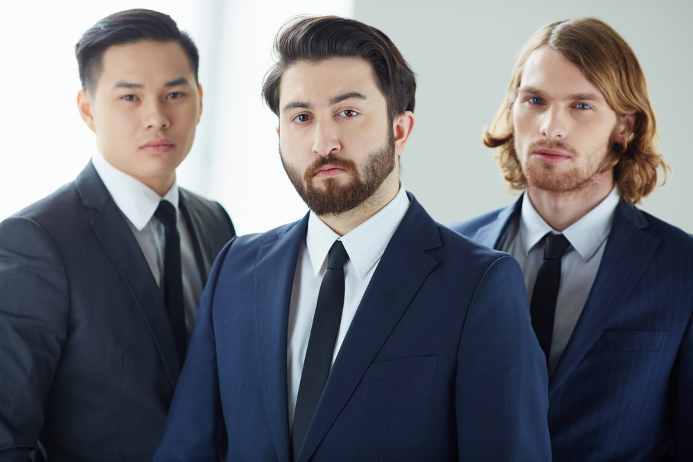 Close-up Portrait Of A Serious Bearded Businessman With His Colleagues On The Background