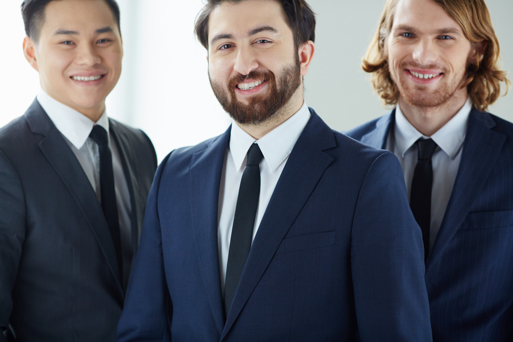 Smiling Businessman Looking At Camera With His Colleagues On Background