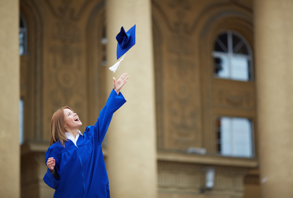 Portrait Of Lovely Student Throwing Graduation Hat