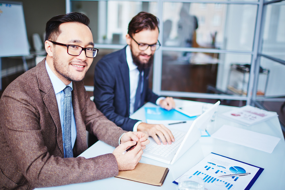 Young Businessman In Eyeglasses Looking At Camera In Working Environment