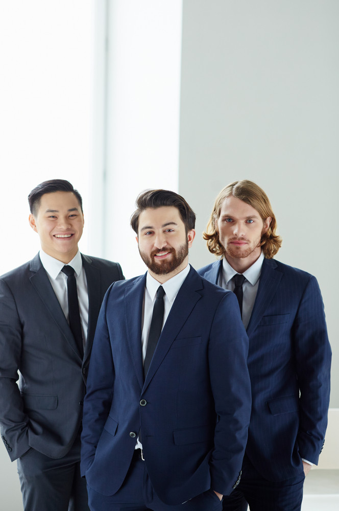 Young Businessman Looking At Camera With His Colleagues On Background