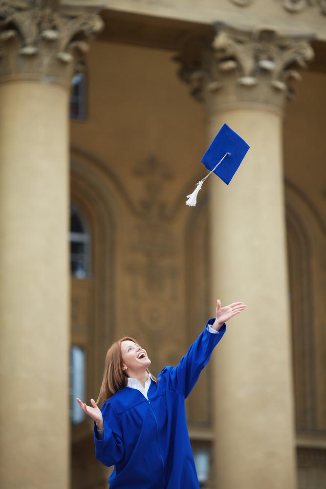 Portrait Of Joyful Student Throwing Graduation Hat