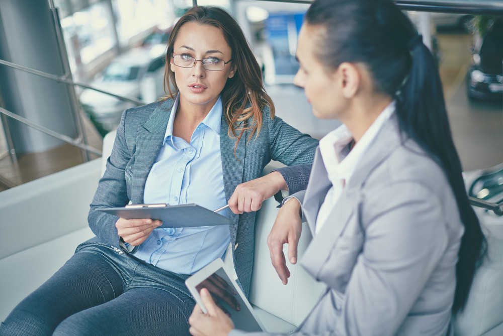 Image Of Pensive Businesswoman Looking At Camera While Discussing Working Plan With Colleague