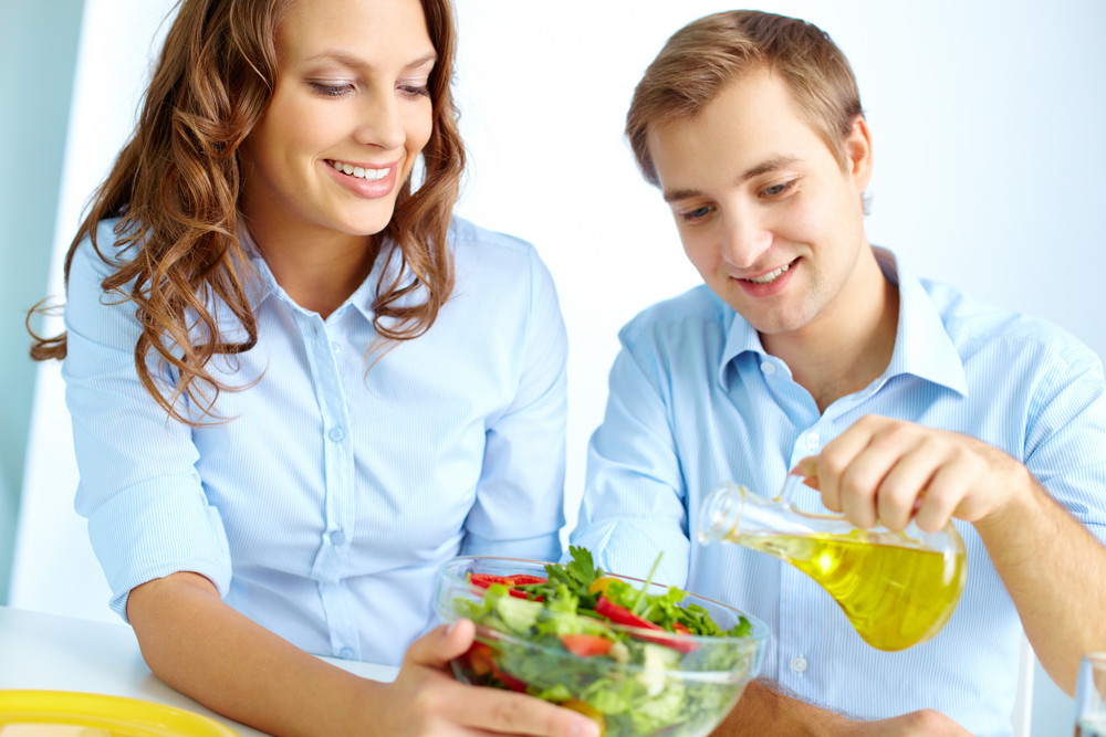 Happy Man Pouring Oil Into Vegetable Salad With His Wife Near By