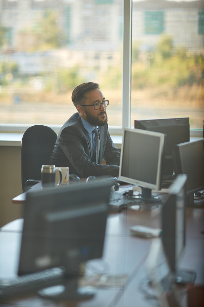 Busy Asian Manager Working With Computer In Office