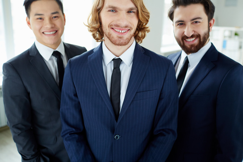 Young Businessman Looking At Camera On Background Of Partners