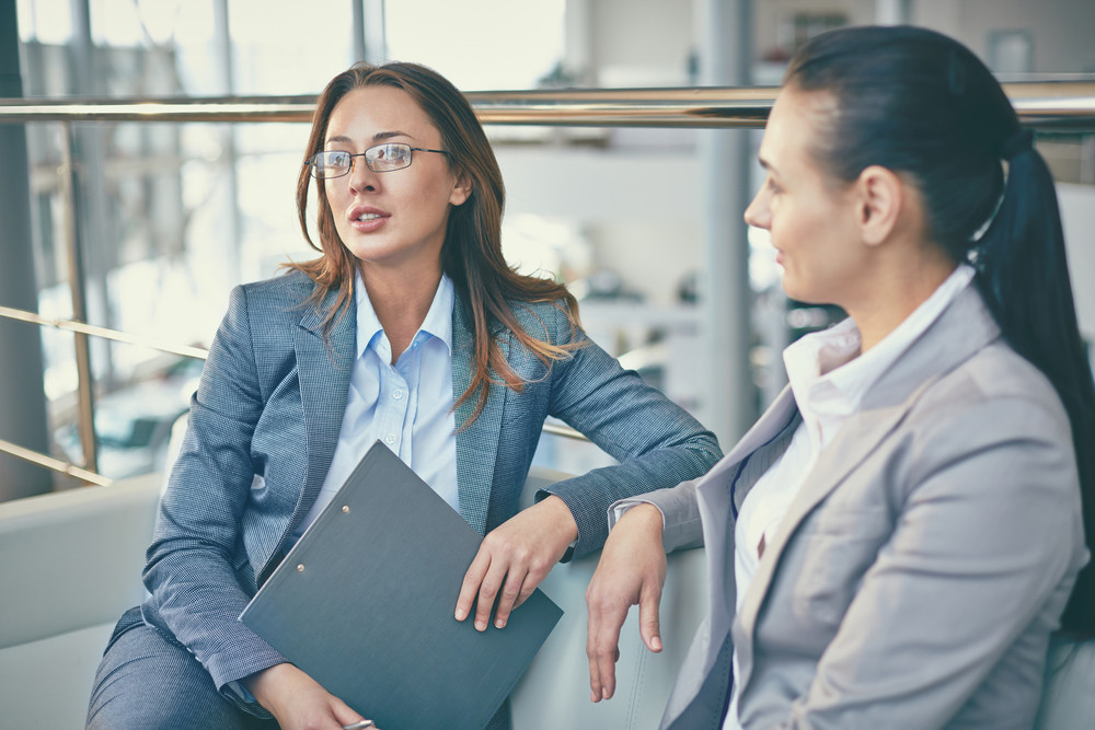 Image Of Pensive Businesswoman With Clipboard Telling Something To Her Colleague