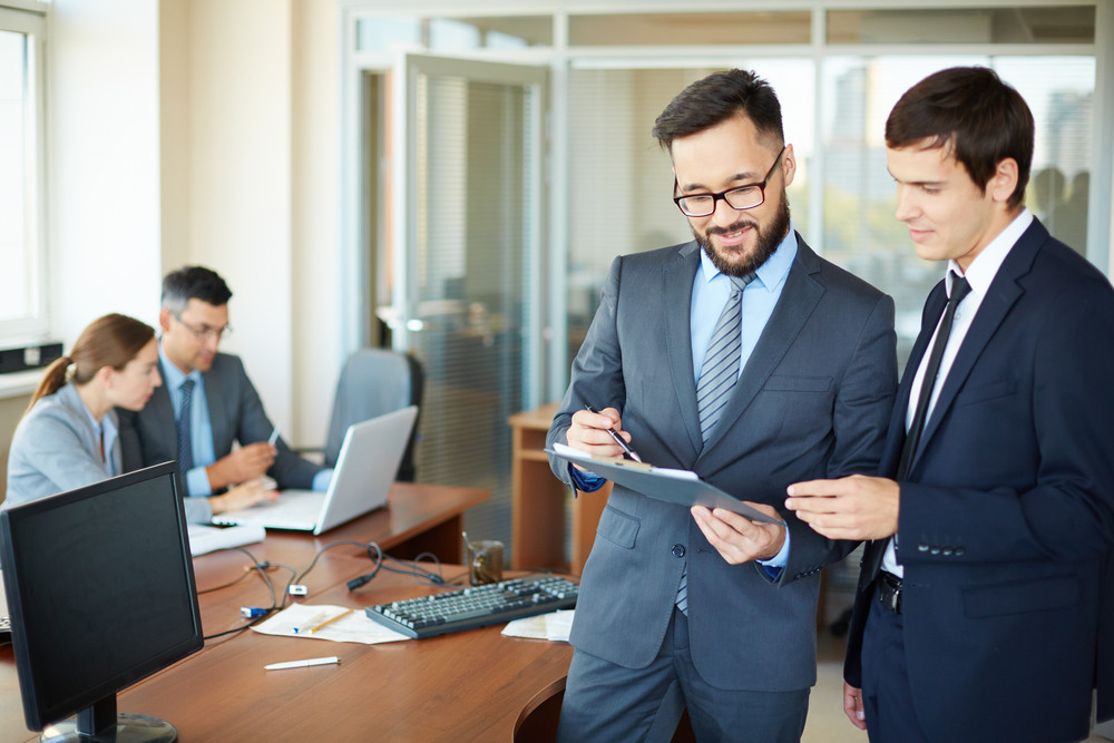 Confident Businessman With Clipboard Consulting His Partner On Background Of Their Colleagues In Office