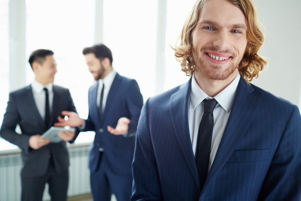 Young Businessman Looking At Camera In Working Environment