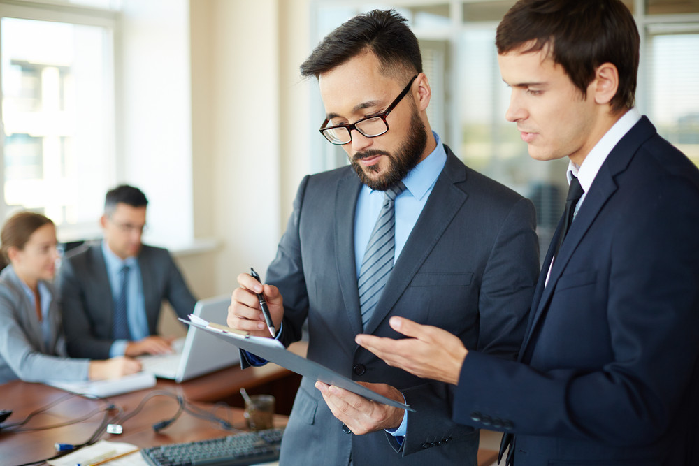 Asian Businessman Pointing At Document While Consulting His Partner On Background Of Their Two Colleagues