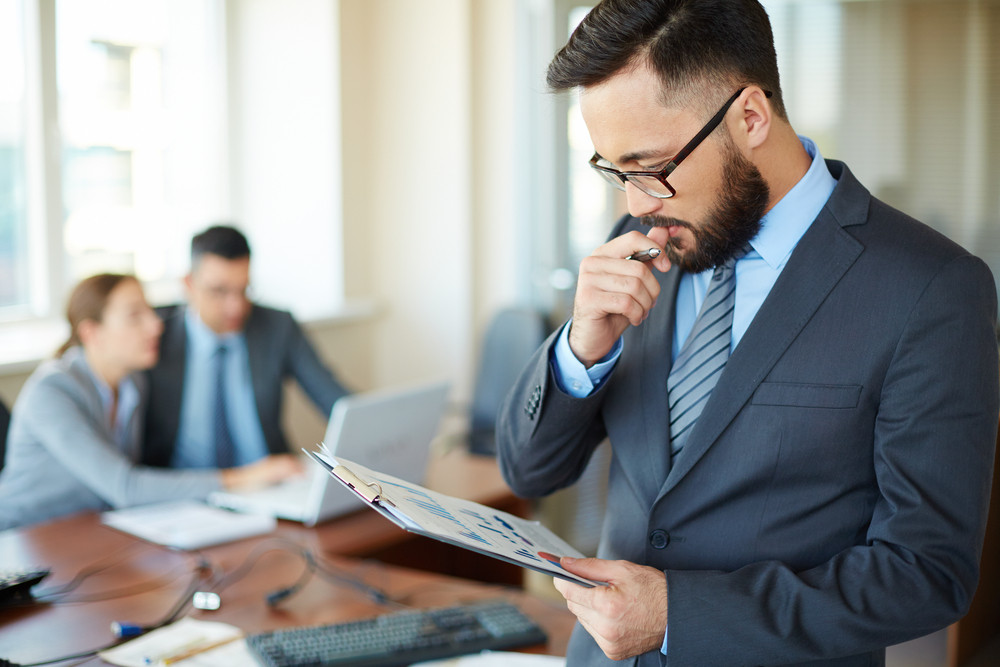Asian Businessman Looking At Document In Office On Background Of Two Colleagues