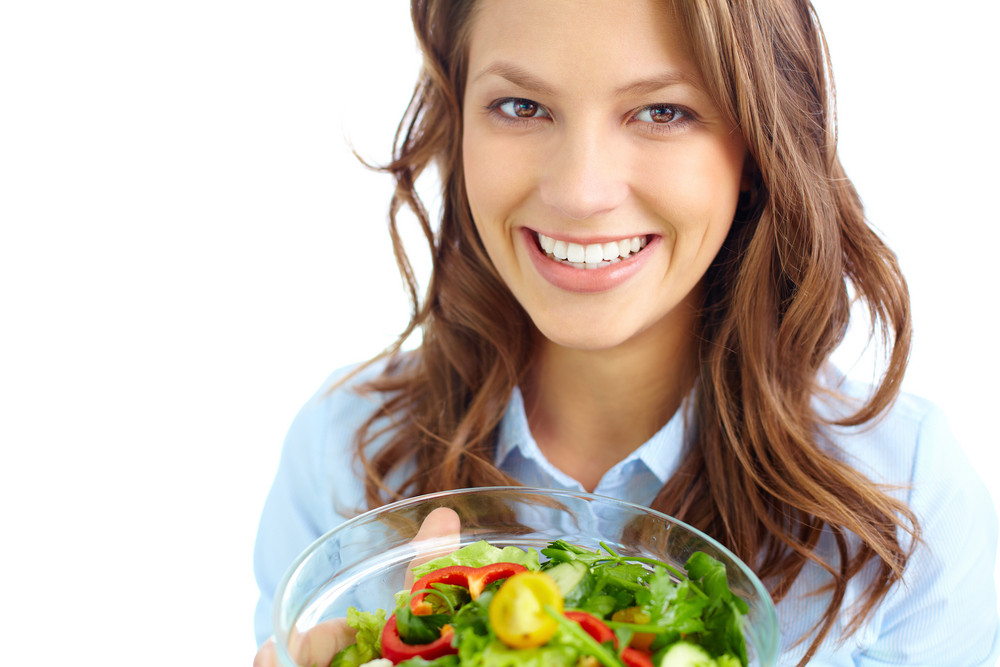 Close-up Of Pretty Girl Holding Fresh Vegetable Salad In Glass Bowl And Looking At Camera