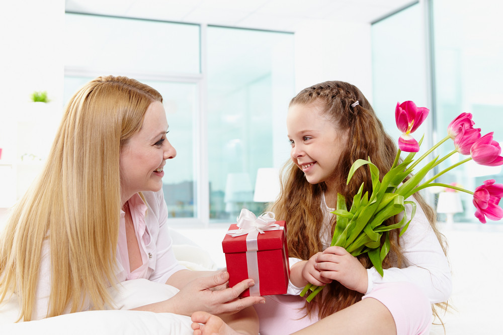 Adorable Girl With Bunch Of Beautiful Tulips Looking At Her Mother With Giftbox