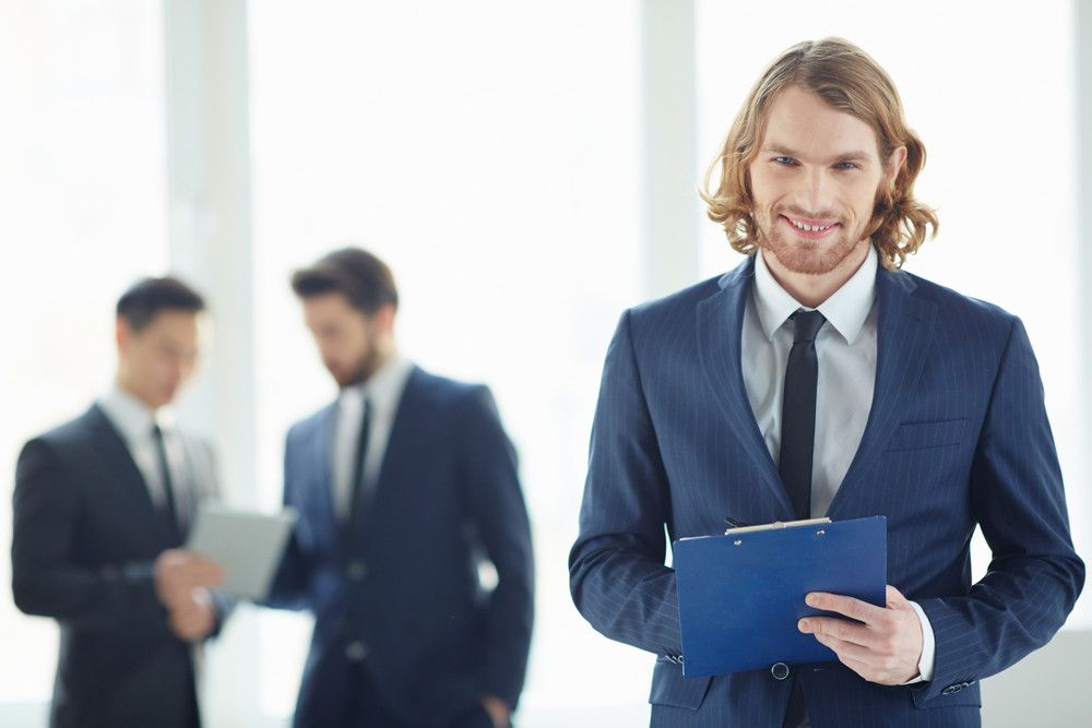 Young Businessman With Clipboard Looking At Camera In Working Environment