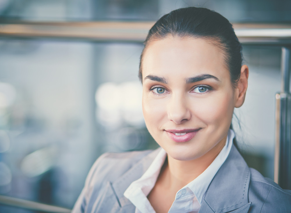 Young Businesswoman Looking At Camera With Toothy Smile
