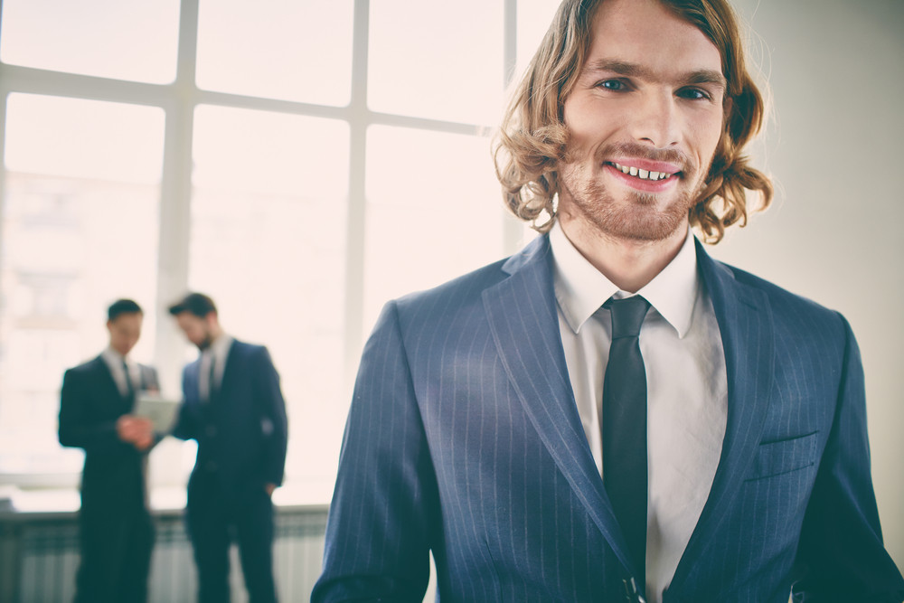Closeup Portrait Of A Young Businessman Smiling And Posing At Camera On The Foreground