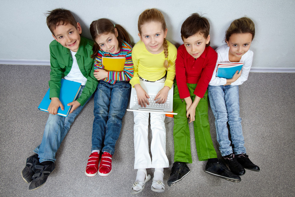 Portrait Of Five Pupils Looking At Camera While Sitting On The Floor Of Classroom