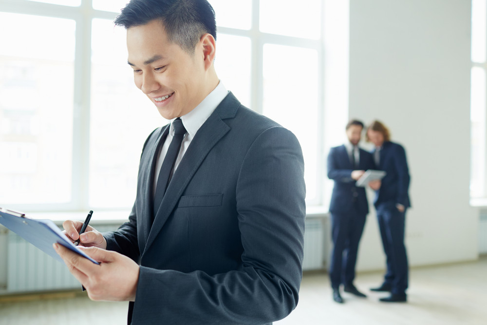 Young Businessman With Clipboard Writing Plan In Working Environment