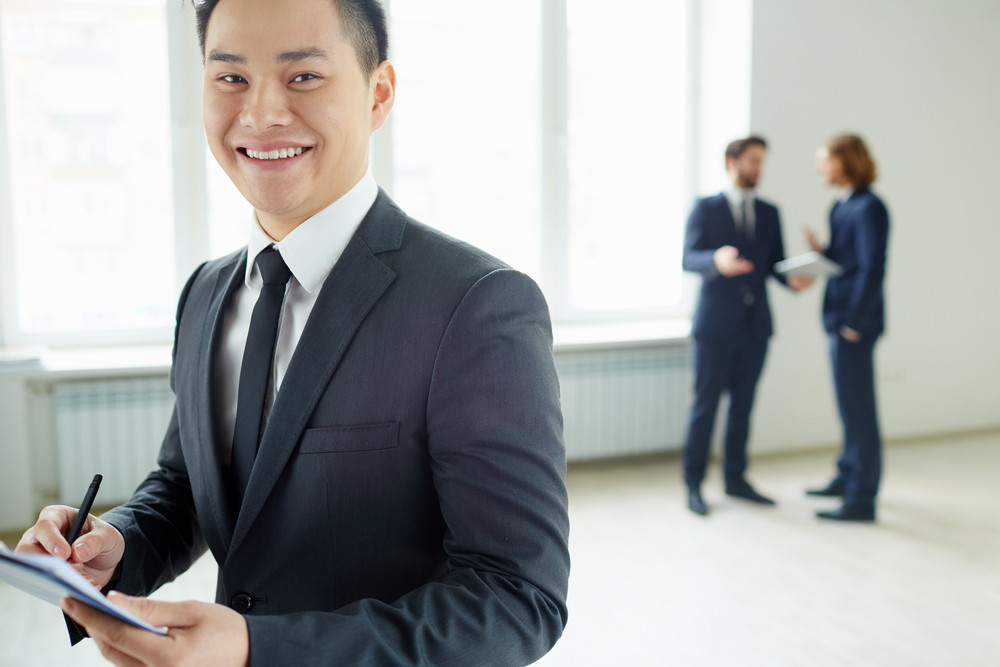 Businessman Smiling At Camera While Signing A Document