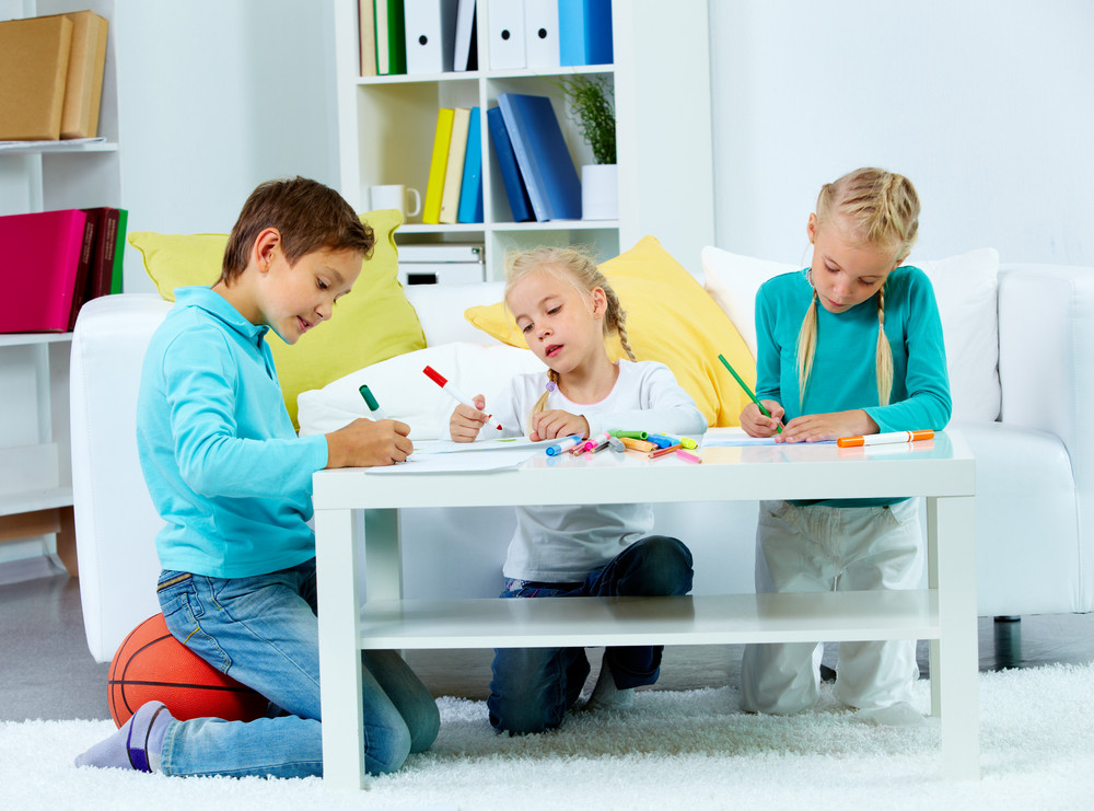 Portrait Of Three Children Drawing At Home