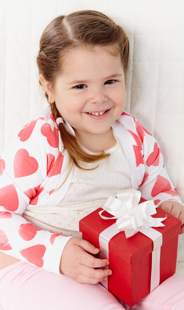 Portrait Of Happy Girl With Giftbox Looking At Camera And Smiling