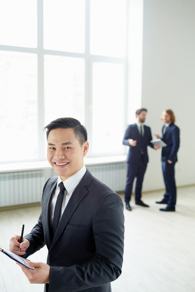 Young Businessman With Clipboard Writing Plan And Looking At Camera In Working Environment