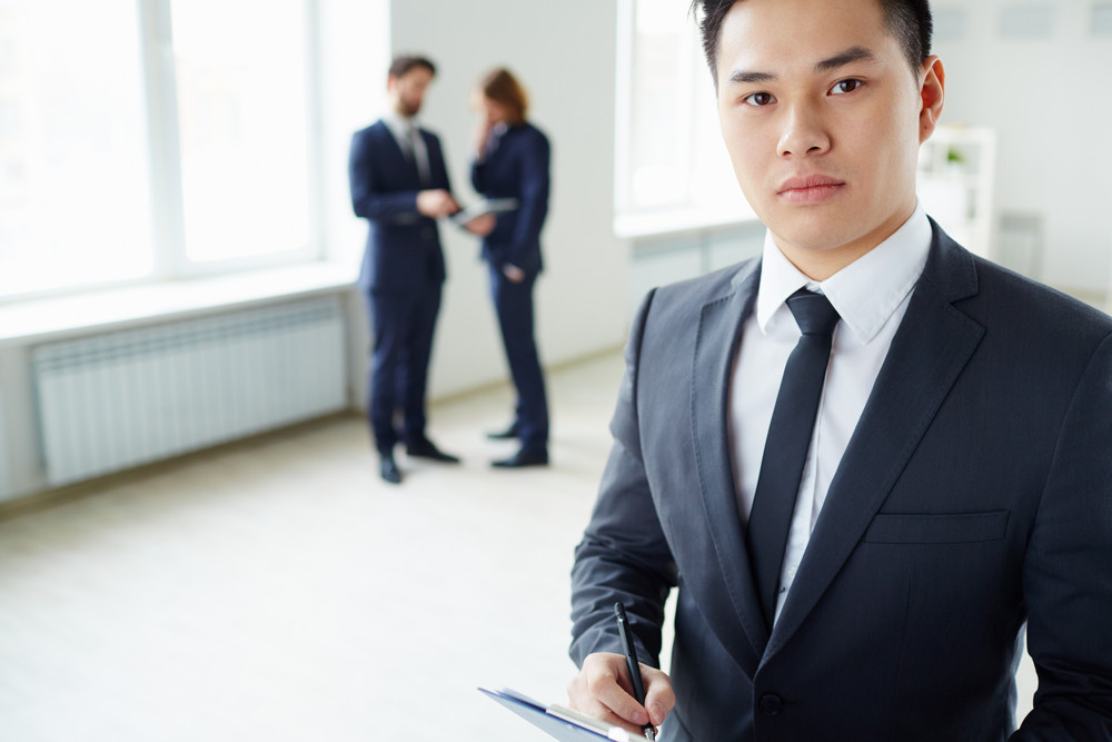 Young Businessman Writing Plan And Looking At Camera In Working Environment
