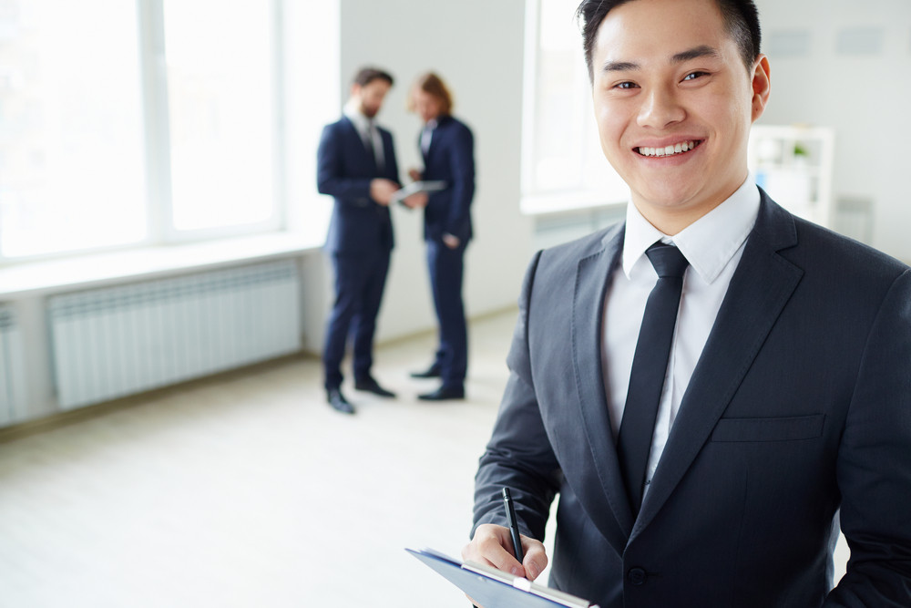 Young Successful Manager Looking At Camera While His Colleagues Talking On The Background