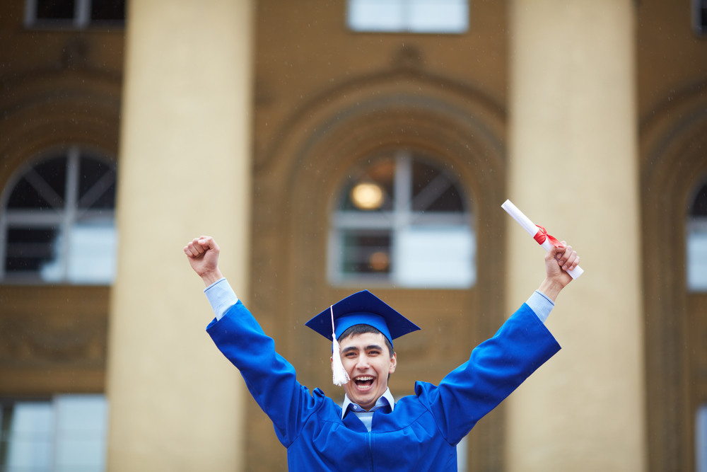Portrait Of Confident Student With Graduation Certificate Showing Gladness