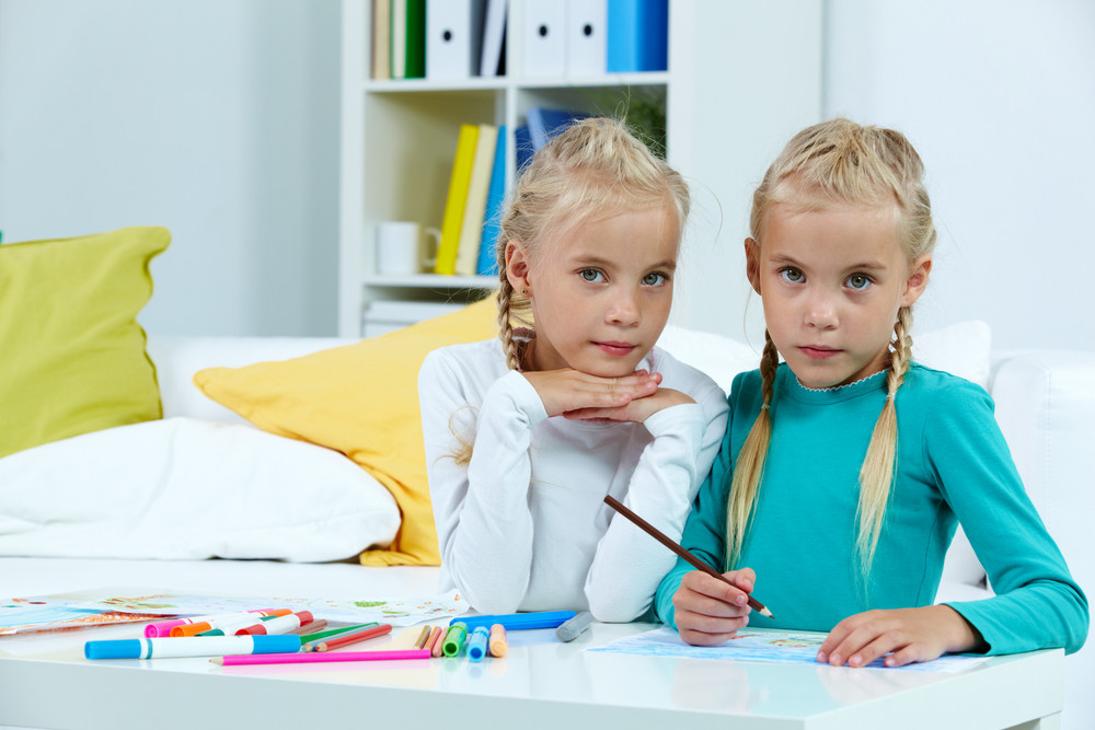 Portrait Of Lovely Twins Drawing With Colorful Pencils