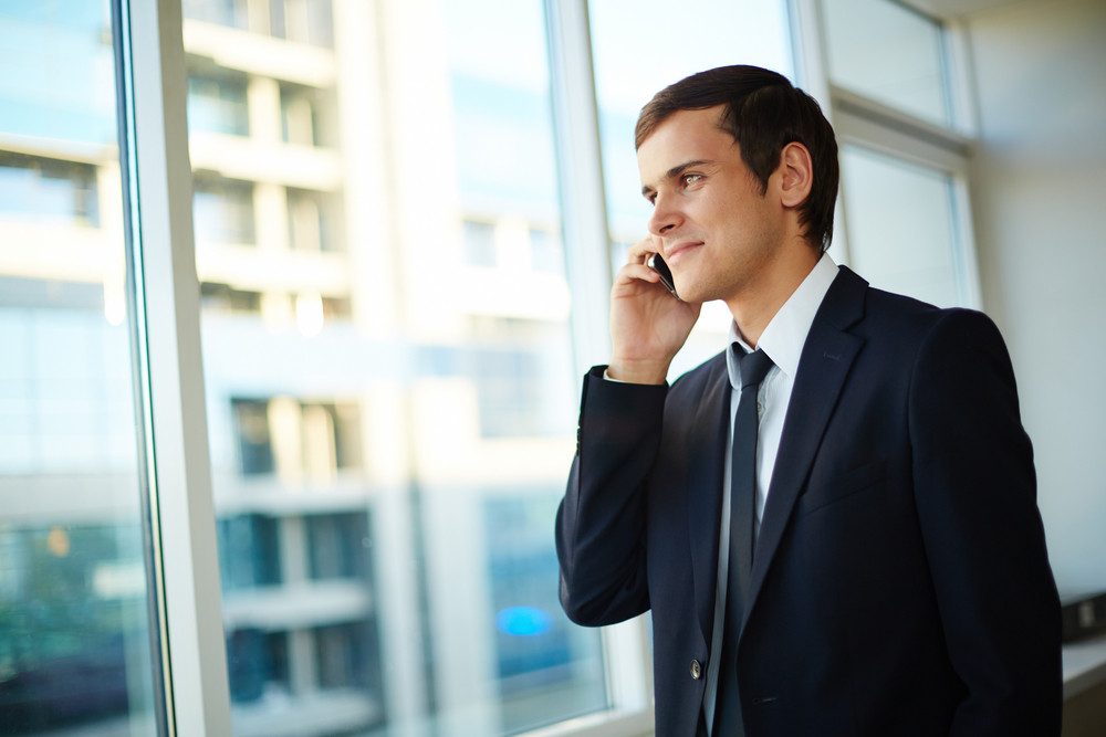 Elegant Businessman Speaking On Cellphone And Looking Through Window