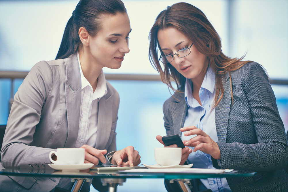 Image Of Two Friendly Businesswomen Using Modern Technologies In Office